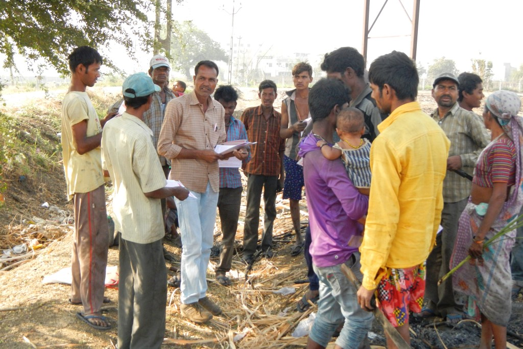 A member of Prayas distributes information material among the workers on a sugarcane field.